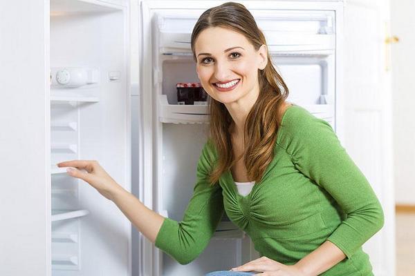 Une fille se tient près du réfrigérateur ouvert