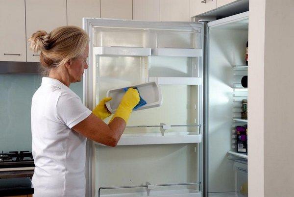Femme lave un frigo