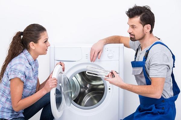En man och en kvinna i närheten av tvättmaskinen