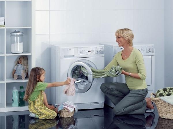 Anne ve kızı çamaşır makinesinin yanında