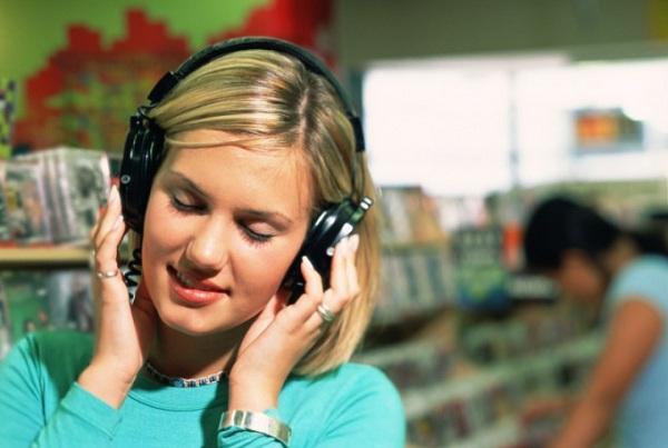 Pige lytter til musik på hovedtelefoner