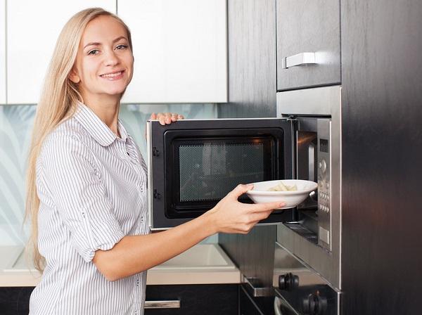 Femme met une assiette au micro-ondes