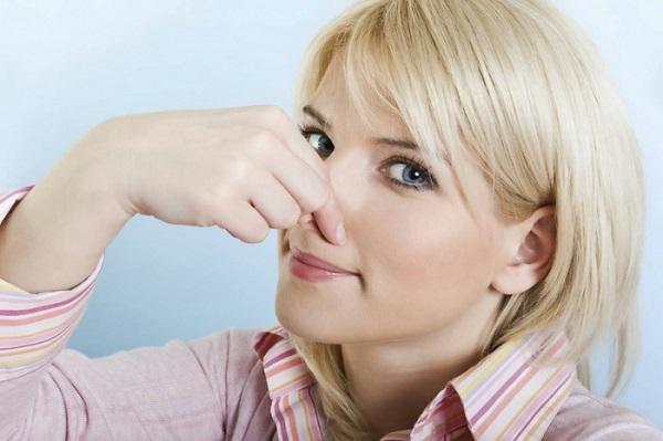 Fille couvre son nez avec sa main
