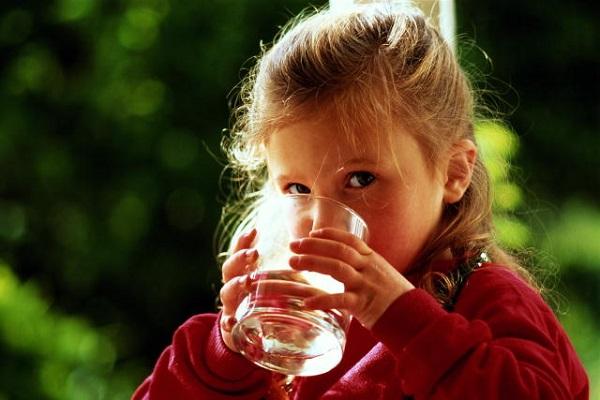 बच्चा एक गिलास से पानी पीता है