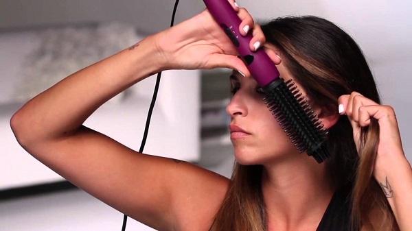 La fille sèche ses cheveux avec un sèche-cheveux