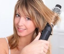 Girl dries her hair with a blow-brush