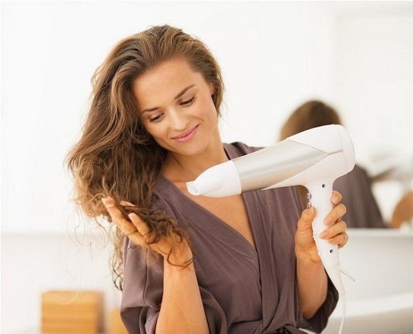 Jeune femme sèche les cheveux