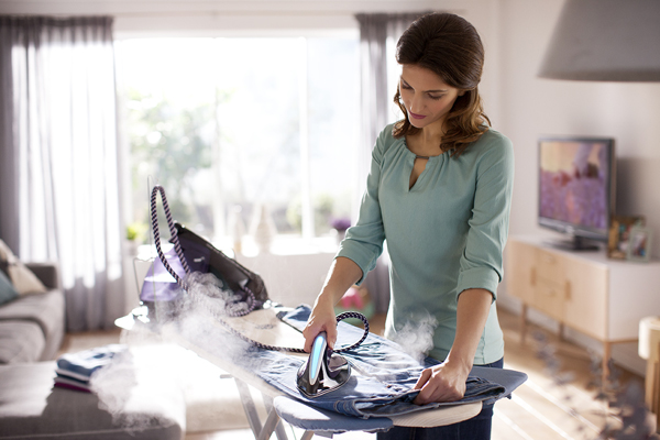 Girl strokes an iron with a steam generator