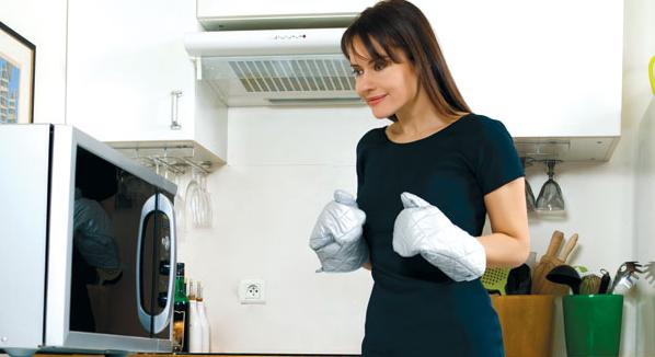 Mikrodalga fırın yakınındaki mutfak eldivenleri kız