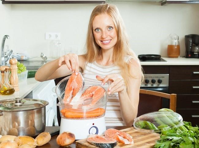 Genç kadın bir çift kazanda yemek yapıyor.
